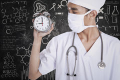 A doctor holding alarm clock Royalty Free Stock Photography