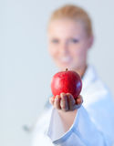 Doctor holding an apple with focus on the apple. Doctor with an apple on her hand Stock Photos
