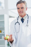 Doctor holding an apple Stock Images
