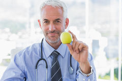 Doctor holding an apple in his hand Stock Photos
