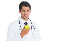 Doctor holding an apple and smiling at camera Royalty Free Stock Image