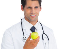 Doctor holding an apple and smiling Stock Photo