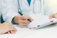 Doctor holding application form while consulting patient ,close up of patient and doctor taking notes,medical content,medical back. Ground and selective focus royalty free stock photo