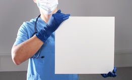 Doctor holding blank banner , standing on white background Royalty Free Stock Image