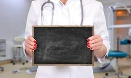 Doctor holding blank chalk board Stock Photo
