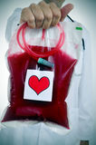 Doctor holding a blood bag with a sticker of a red heart Stock Photography