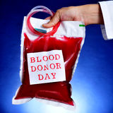 Doctor holding a blood bag with the text blood donor day Royalty Free Stock Image