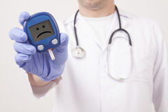 Doctor holding blood sugar meter. Sad smiley face Stock Photos