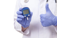 Doctor holding blood sugar meter. Showing OK sign Stock Images