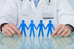 Doctor holding blue paper people chain at desk Royalty Free Stock Photography
