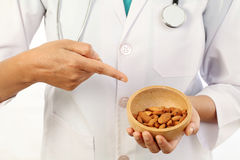 Doctor holding a bowl of almonds Royalty Free Stock Image