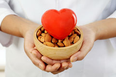 Doctor holding a bowl of almonds and heart shape - Health concept Stock Photo