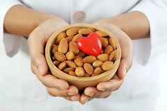 Doctor holding a bowl of almonds and heart shape Stock Photo