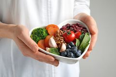 Doctor holding bowl with products for heart-healthy diet. Closeup stock photo