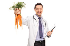 Doctor holding a bunch of carrots Royalty Free Stock Photography