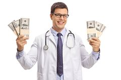 Doctor holding bundles of money and smiling Royalty Free Stock Photos