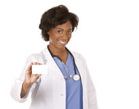 Doctor holding business card. Black nurse wearing scrubs on white isolated background Royalty Free Stock Images