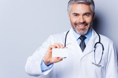 Doctor holding business card. Cheerful mature doctor showing his business card and smiling while standing against grey background Stock Images