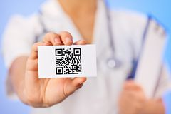 Doctor holding business card with QR code Stock Photo