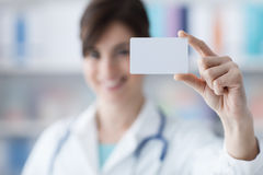 Doctor holding a business card Royalty Free Stock Image