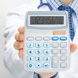 Doctor holding calculator in hand - health care concept - close up Stock Photos