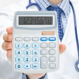 Doctor holding calculator in hand - health care concept - studio shot Royalty Free Stock Photography