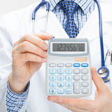 Doctor holding calculator in hands - close up Stock Images