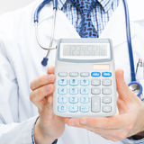 Doctor holding calculator in hands - health care concept - close up shot Stock Image