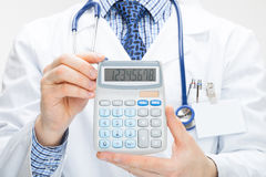 Doctor holding calculator in hands - health care concept - studio shot Royalty Free Stock Photography