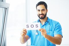 Doctor holding a card with symbol Sos, Medical concept.  stock images