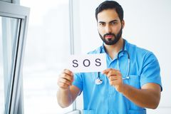 Doctor holding a card with symbol Sos, Medical concept.  stock photo