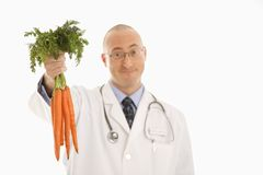Doctor holding carrots. Royalty Free Stock Images
