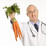 Doctor holding carrots. Stock Photo