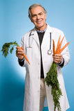 Doctor holding carrots Royalty Free Stock Photos