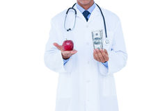 Doctor holding cash and red apple Royalty Free Stock Photos
