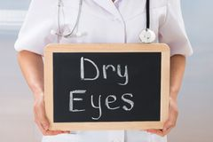 Doctor holding chalkboard with the text dry eyes Royalty Free Stock Photography