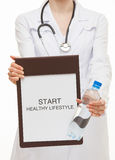 Doctor holding a clipboard and calling to healthy lifestyle Stock Image