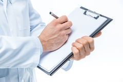 Doctor holding clipboard. Close-up partial view of male doctor holding clipboard and writing on white blank paper Royalty Free Stock Image