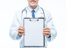 Doctor holding clipboard. Partial view of smiling male doctor holding clipboard on white stock images