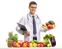 Doctor holding a clipboard and a plate behind a table with fruit. Doctor holding a clipboard and a plate behind a table with t and vegetables isolated on white royalty free stock photos