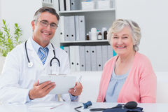 Doctor holding clipboard while sitting with senior patient Stock Image
