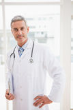 Doctor holding clipboard smiling at camera Royalty Free Stock Photography