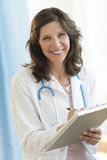 Doctor Holding Clipboard While Standing In Clinic Royalty Free Stock Images