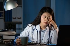 Doctor holding coffee tired after busy day Royalty Free Stock Images