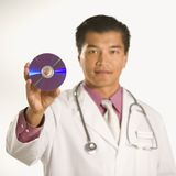 Doctor holding compact disc. Stock Photo