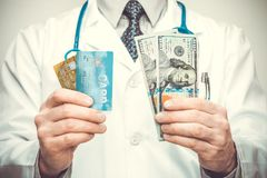 Doctor holding credit cards in his left and USA dollars in his right hand royalty free stock photography
