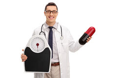 Doctor holding a diet pill and a weight scale Royalty Free Stock Image