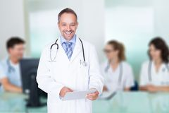 Doctor holding digital tablet against team in meeting room Royalty Free Stock Photography
