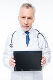 Doctor holding digital tablet. Male doctor holding digital tablet and looking at camera on white Stock Image