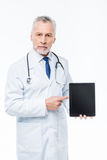 Doctor holding digital tablet. Male doctor holding digital tablet and pointing with finger at blank screen Royalty Free Stock Photo